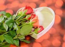 Les roses oranges et rouges fleurit avec le boîte-cadeau de forme de coeur, fond rouge de bokeh Photographie stock