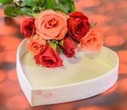 Les roses oranges et rouges fleurit avec le boîte-cadeau de forme de coeur, fond rouge de bokeh Image libre de droits