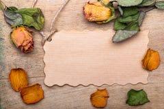 Les roses oranges sèches et vident la carte de papier sur le fond en bois, Image stock
