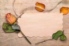 Les roses oranges sèches et vident la carte de papier sur le fond en bois, Photographie stock libre de droits