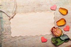 Les roses oranges sèches et vident la carte de papier sur le fond en bois Photo stock