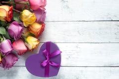 Les roses pourpres et jaunes, enferment dans une boîte le présent sur le fond en bois blanc Photos stock