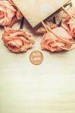 Les roses roses dans le panier avec le message d'amour se connectent le fond clair, vue supérieure Pastel modifié la tonalité Photos stock