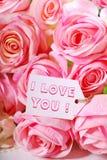 Les roses roses et l'étiquette de papier avec amour textotent Image libre de droits