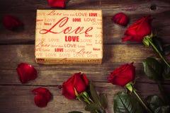 Les roses rouges et le cadeau ont couvert le papier de métier sur le fond en bois, dessus Image stock