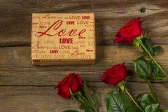 Les roses rouges et le cadeau ont couvert le papier de métier sur le fond en bois, dessus Photographie stock libre de droits