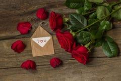 Les roses rouges fleurissent et les pétales et l'enveloppe avec le texte je t'aime Photos libres de droits
