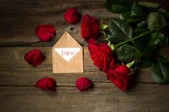 Les roses rouges fleurissent et les pétales et l'enveloppe avec le texte je t'aime Image libre de droits