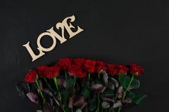 Les roses rouges fleurit avec le mot en bois AMOUR sur le fond noir avec Photo libre de droits