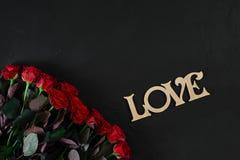 Les roses rouges fleurit avec le mot en bois AMOUR sur le fond noir avec Images libres de droits