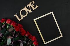 Les roses rouges fleurit avec le mot en bois AMOUR sur le fond noir avec Image stock