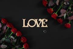 Les roses rouges fleurit avec le mot en bois AMOUR sur le fond noir avec Photos stock