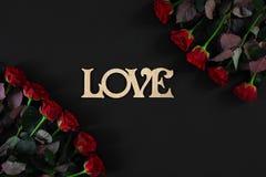 Les roses rouges fleurit avec le mot en bois AMOUR sur le fond noir avec Photographie stock