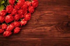 Les roses rouges fraîches plus de noient le fond en bois Images libres de droits