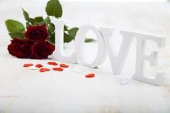 Les roses rouges, les coeurs et le mot aiment sur un fond en bois Photo stock
