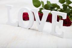 Les roses rouges, les coeurs et le mot aiment sur un fond en bois Photographie stock