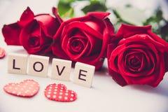 Les roses rouges sont placées sur un fond blanc et le le en bois Photos libres de droits
