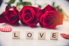 Les roses rouges sont placées sur un fond blanc et le le en bois Photographie stock