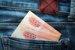 Les roubles russes d'argent dans des blues-jean empochent comme image de vue supérieure Photographie stock
