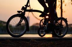 Les roues de vélo se ferment vers le haut de l'image sur la route de coucher du soleil d'asphalte photographie stock libre de droits