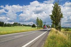 Les routes avec l'allée de peuplier, viennent de loin deux camions rouges et de beaucoup de voitures Images stock