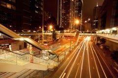 Les rues sombres avec des hôtels, des gratte-ciel et des lignes de mouvement près de tram de ville s'arrêtent Photographie stock libre de droits