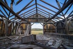 Les ruines d'un bâtiment en bois sur la prairie, vues de l'intérieur Images stock