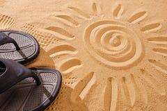 Les sables de pantoufles sur la plage dans le sable ont collé aux espadrilles avec le soleil Images stock