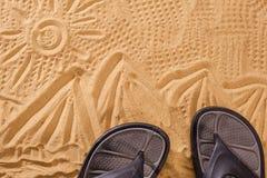Les sables de pantoufles sur la plage dans le sable ont collé aux espadrilles avec le soleil Photographie stock