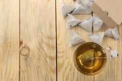 Les sacs à thé de pyramide tombent hors de la boîte sur une table en bois naturelle Vue supérieure avec l'espace pour le texte images stock