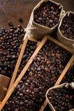 Les sacs de jute et les récipients en bois ont rempli de haricots de cofee Image libre de droits