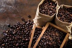 Les sacs de jute et les récipients en bois ont rempli de haricots de cofee Image stock