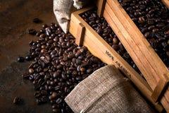 Les sacs de jute et les récipients en bois ont rempli de haricots de cofee Photographie stock