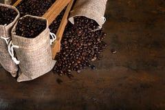 Les sacs de jute et les récipients en bois ont rempli de haricots de cofee Photos stock