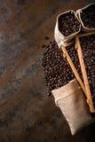 Les sacs de jute et les récipients en bois ont rempli de haricots de cofee Photos libres de droits
