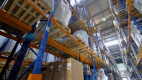 Les sacs et les boîtes se reposent sur des supports d'entrepôt dans une basse vue clips vidéos