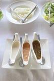 Les salades sauce dans une tasse et une variété blanches de saveurs photographie stock libre de droits