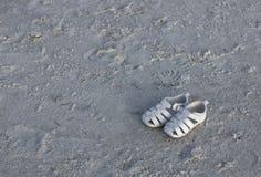 Les sandales abandonnent sur la plage Photo stock