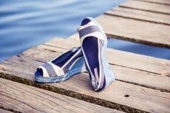 Les sandales bleues de denim se trouvent sur l'embrayage en bois au lac Photos stock