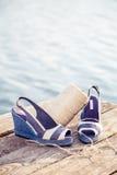 Les sandales bleues de denim se trouvent sur l'embrayage en bois au lac Photo stock