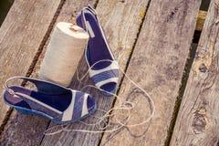 Les sandales bleues de denim se trouvent sur l'embrayage en bois au lac Photographie stock libre de droits