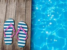 Les sandales de bascule électronique sur de vieux conseils en bois s'approchent de la piscine Photographie stock