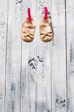 Les sandales des enfants accrochant sur une corde à linge. Photo stock