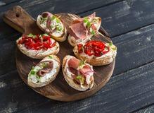 Les sandwichs avec du fromage de chèvre, anchois, ont rôti les poivrons, jambon sur un conseil rustique en bois Image stock