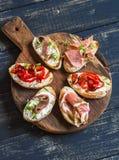 Les sandwichs avec du fromage de chèvre, anchois, ont rôti les poivrons, jambon sur un conseil rustique en bois Photos libres de droits