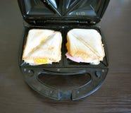 Les sandwichs avec du fromage et la saucisse dans un sandwich électrique noir font des emplettes Images stock