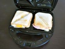 Les sandwichs avec du fromage et la saucisse dans un sandwich électrique noir font des emplettes Photographie stock libre de droits