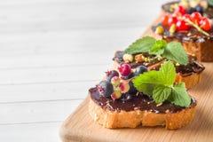 Les sandwichs avec la pâte de chocolat, les pistaches et les baies fraîches sur une portion en bois embarquent Copiez l'espace image libre de droits