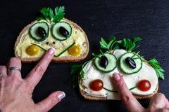 Les sandwichs drôles sur les mains de conseil et de femme d'ardoise images stock
