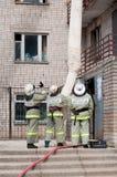Les sapeurs-pompiers évacuent des résidents à l'aide d'un dispositif de délivrance du feu images libres de droits